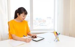 有片剂个人计算机的在家学会亚裔学生的女孩 图库摄影