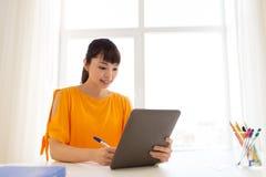 有片剂个人计算机的在家学会亚裔学生的女孩 库存照片