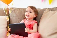 有片剂个人计算机的女婴在生日聚会在家 免版税库存图片