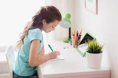 有片剂个人计算机的女孩在家写给笔记本的 库存图片