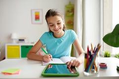 有片剂个人计算机的女孩在家写给笔记本的 免版税库存照片