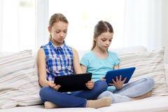有片剂个人计算机的女孩在家坐沙发 免版税库存照片