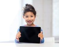 有片剂个人计算机的女孩在家 免版税库存照片