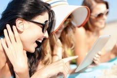 有片剂个人计算机的女孩在海滩 免版税库存照片