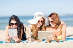 有片剂个人计算机的女孩在海滩 免版税库存图片