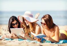 有片剂个人计算机的女孩在海滩 库存照片