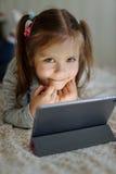有片剂个人计算机的女孩 免版税库存图片
