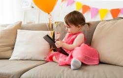 有片剂个人计算机的女婴在生日聚会在家 免版税库存照片