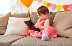 有片剂个人计算机的女婴在生日聚会在家 库存照片