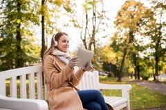 有片剂个人计算机的妇女和耳机在秋天停放 免版税库存照片