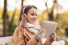 有片剂个人计算机的妇女和耳机在秋天停放 免版税库存图片