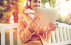 有片剂个人计算机的妇女和耳机在秋天停放 免版税图库摄影