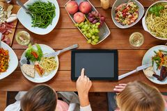 有片剂个人计算机的妇女在充分桌上食物 免版税库存照片