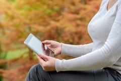 有片剂个人计算机的妇女在她的手上 库存照片