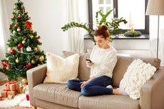 有片剂个人计算机的妇女在家在圣诞节 免版税库存图片