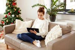 有片剂个人计算机的妇女在家在圣诞节 免版税库存照片