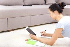 有片剂个人计算机的妇女在家 免版税库存图片