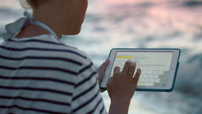 有片剂个人计算机的妇女由海在大风天 影视素材