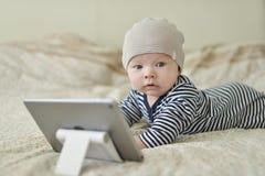 有片剂个人计算机的婴孩 库存图片