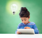 有片剂个人计算机的小女孩在学校 免版税库存图片