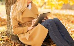 有片剂个人计算机的少妇在秋天公园 库存照片