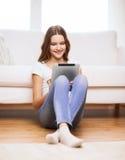有片剂个人计算机的微笑的十几岁的女孩在家 库存照片