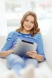 有片剂个人计算机的微笑的十几岁的女孩在家 图库摄影