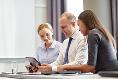 有片剂个人计算机的微笑的商人在办公室 免版税图库摄影