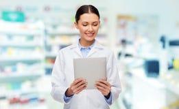 有片剂个人计算机的微笑的女性医生在药房 图库摄影