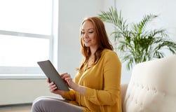 有片剂个人计算机的微笑的妇女坐沙发 库存图片