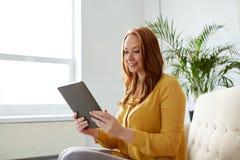 有片剂个人计算机的微笑的妇女坐沙发 免版税库存图片