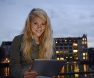 有片剂个人计算机的微笑的妇女 免版税库存图片