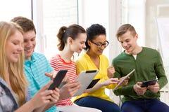有片剂个人计算机的微笑的学生在学校 免版税库存照片