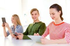 有片剂个人计算机的微笑的学生在学校 库存照片