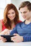 有片剂个人计算机的微笑的学生在学校 免版税库存图片