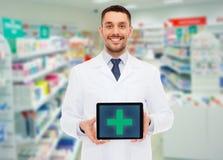 有片剂个人计算机的微笑的男性医生在药房 免版税库存图片