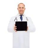 有片剂个人计算机的微笑的男性医生 免版税库存图片
