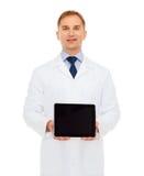 有片剂个人计算机的微笑的男性医生 库存图片