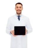 有片剂个人计算机的微笑的男性医生 免版税库存照片