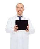 有片剂个人计算机的微笑的男性医生 库存照片