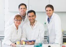 有片剂个人计算机的微笑的科学家在实验室里 图库摄影