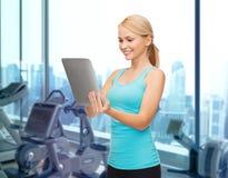 有片剂个人计算机的微笑的运动的妇女在健身房 库存照片