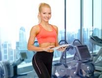 有片剂个人计算机的微笑的运动的妇女在健身房 库存图片