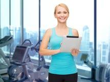 有片剂个人计算机的微笑的运动的妇女在健身房 免版税库存图片