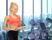 有片剂个人计算机的微笑的运动的妇女在健身房 免版税图库摄影