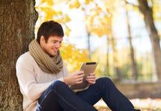 有片剂个人计算机的微笑的年轻人在秋天停放 免版税库存照片
