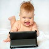 有片剂个人计算机的微笑的婴孩在家 免版税库存照片