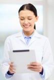 有片剂个人计算机的微笑的年轻医生在内阁 免版税库存图片