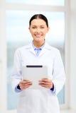有片剂个人计算机的微笑的年轻医生在内阁 图库摄影