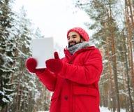有片剂个人计算机的愉快的人在冬天森林里 库存照片